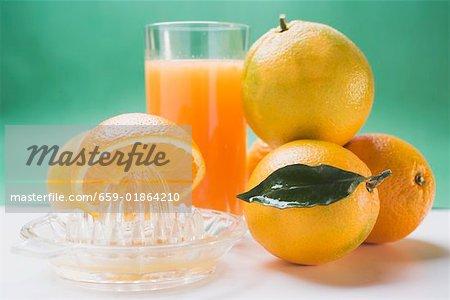 Glass of orange juice, several oranges and citrus squeezer