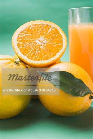 Glass of orange juice and several oranges (detail)