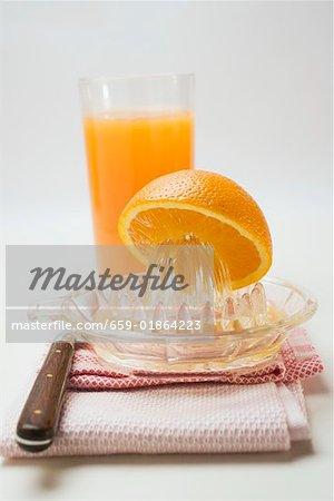 Squeezing an orange, glass of orange juice