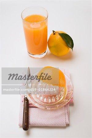 Squeezing an orange, glass of orange juice & whole orange