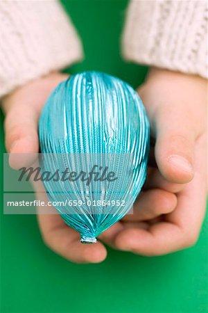 Mains de l'enfant tenant un oeuf de Pâques dans du papier bleu