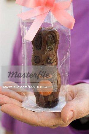 Main tenant un emballage cadeau lapin de Pâques au chocolat