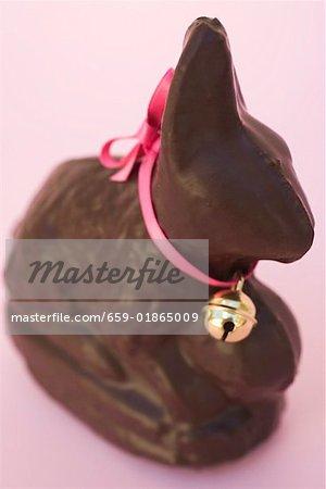 Lapin de Pâques au chocolat avec arc rose et une petite cloche