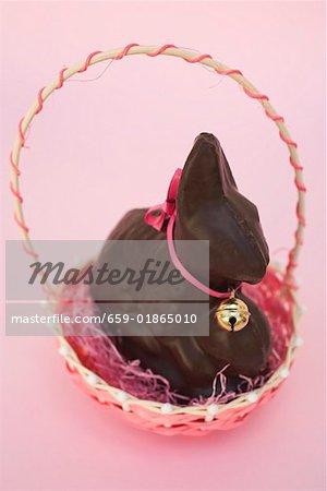 Lapin de Pâques au chocolat avec bow & petite cloche dans le panier de Pâques