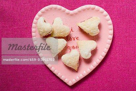 En forme de coeur confiture biscuits sur la plaque rose