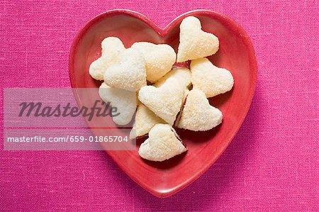 En forme de coeur confiture biscuits dans un plat rouge