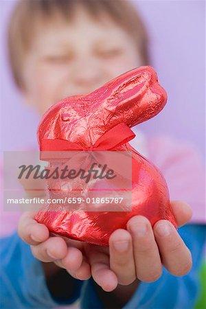 Enfant tenant le lapin de Pâques rouge