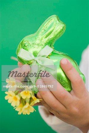 Lapin de Pâques vert de mains de l'enfant