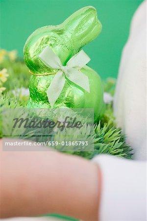 Mains de l'enfant vert lapin de Pâques sur l'herbe