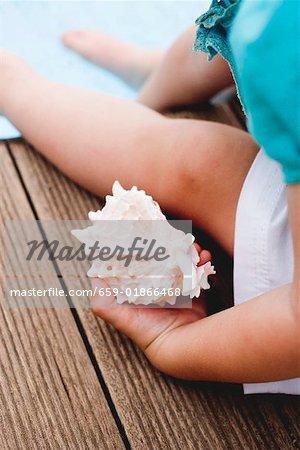 Enfant tenant un coquillage sur le bord de la piscine