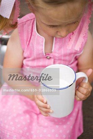 Petite fille tenant la tasse de lait