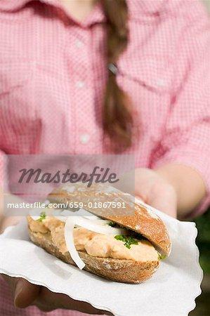 Femme holding pain rouler avec Obatzda (Camembert diffuser) & oignons