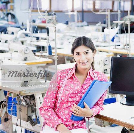 Portrait d'un créateur de mode féminin tenant une file dans l'industrie textile et souriant