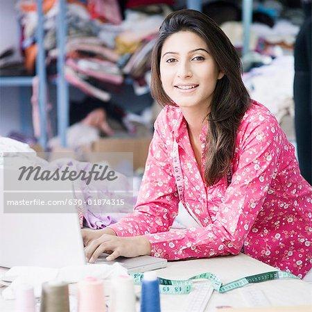 Portrait d'un créateur de mode féminin à l'aide d'un ordinateur portable dans une industrie textile et souriant