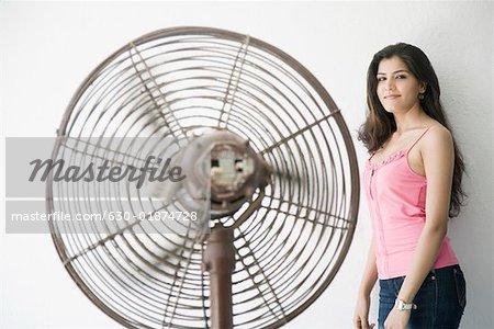 Portrait of a young woman standing near a fan
