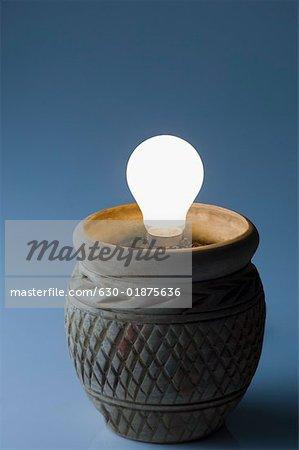 Close-up of a lit light bulb in a pot