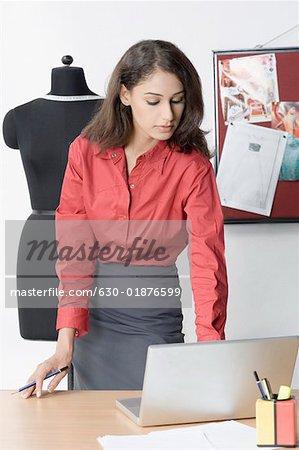 Debout designer de mode féminine et à l'aide d'un ordinateur portable
