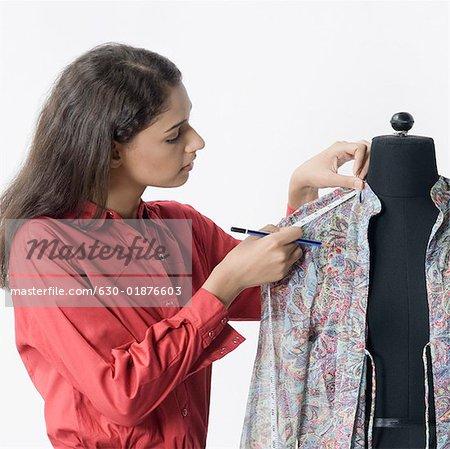 Styliste femelle mesurant le manche d'une chemise