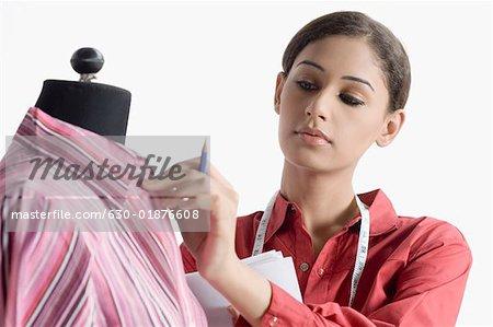 Gros plan d'un créateur de mode féminin une chemise sur un mannequin de réglage