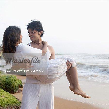 Jeune homme transportant une jeune femme sur la plage, Goa, Inde