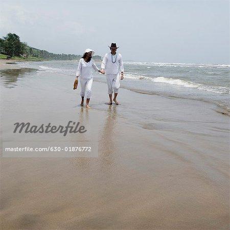Jeune couple marchant avec main dans la main sur la plage
