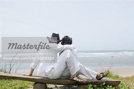 Jeune couple assis sur une planche de bois sur la plage