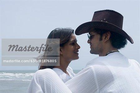Profil de côté d'un jeune couple à la recherche à l'autre sur la plage