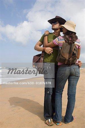 Jeune couple debout sur la plage et d'embrasser l'autre