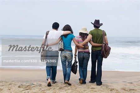 Vue arrière de deux jeunes couples marchant sur la plage avec leurs bras autour de l'autre