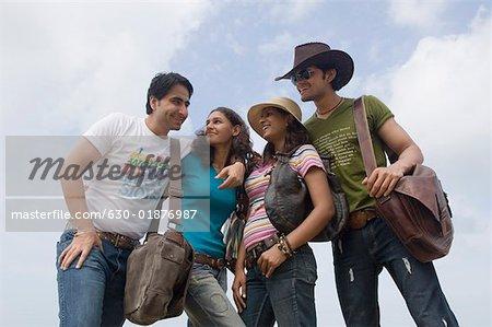 Vue d'angle faible de deux jeunes couples rassemblés et souriant