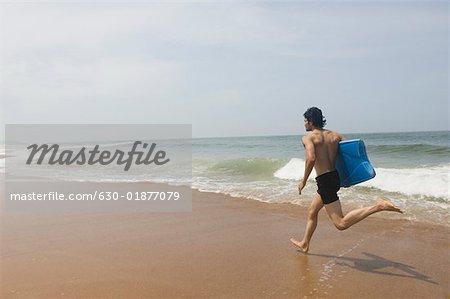 Profil De Cote D Un Jeune Homme Portant Une Planche De Surf Et En