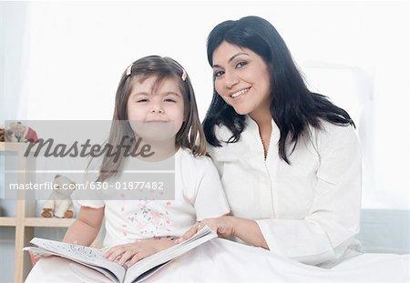 Portrait d'une femme adulte moyenne assis avec sa fille sur le lit et souriant