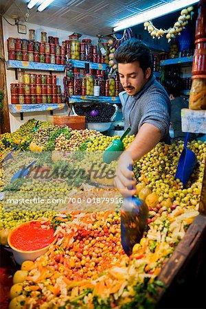 Homme qui vend des Olives en boutique, médina de Fès, Maroc