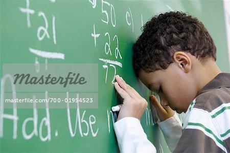 Schüler schreiben auf Tafel