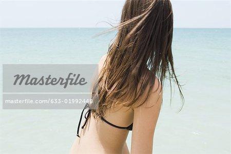 Jeune femme en bikini sur la plage, à la recherche à l'horizon, vue latérale