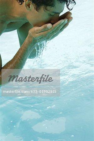 Se penchant sur la piscine, l'eau potable des mains de l'homme