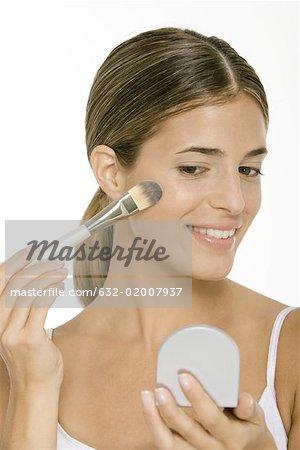 Femme appliquer fard à joues, à la recherche en main mirror