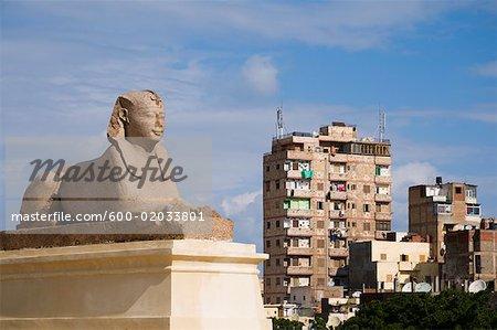 Sphinx, Buildings in Background, Alexandria, Egypt