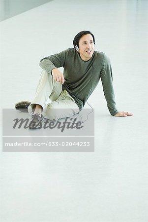 Homme d'âge mûr assis sur le plancher, à l'écoute de MP3 player, pleine longueur