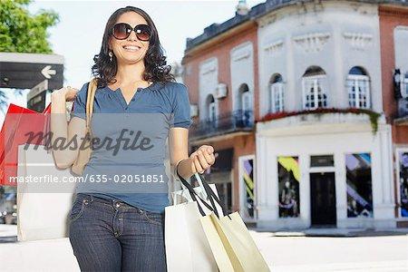 Femme à l'extérieur avec des sacs à provisions souriant