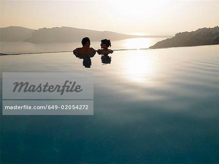 Couple dans la piscine, au coucher du soleil