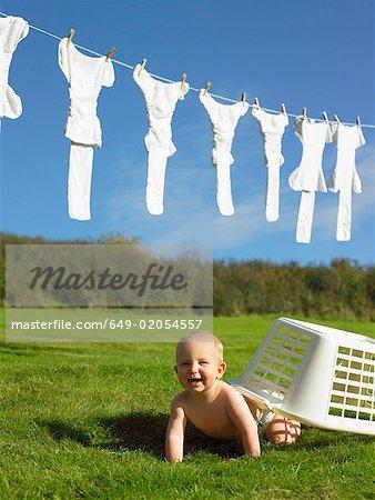 Bébé ramper avec panier de lavage.