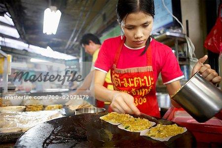 Femme cuisine au marché, Bangkok, Thaïlande
