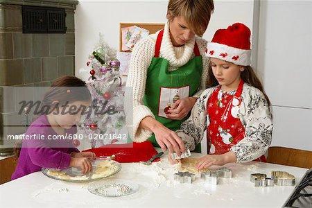 Mutter und Töchter machen Weihnachtsplätzchen