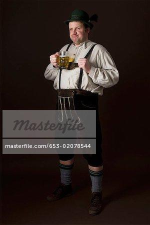 Homme allemand stéréotypée en costume bavarois, tenant une bière