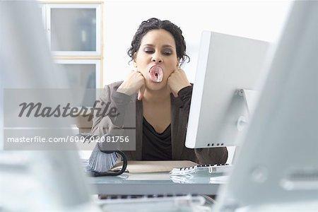 Geschäftsfrau, die sitzen am Schreibtisch kauen Kaugummi