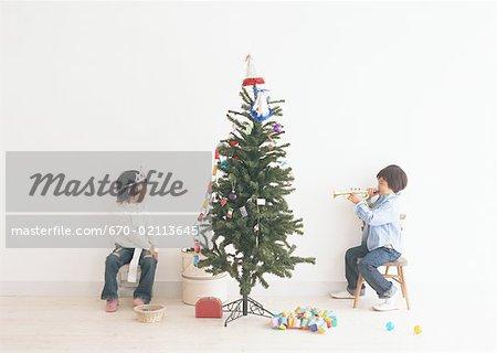 Enfants jouant autour de l'arbre de Noël