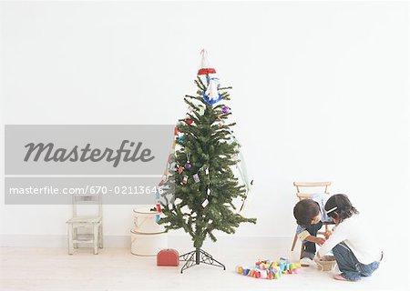 Enfants jouant autour d'un arbre de Noël