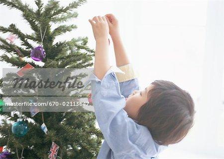 Garçon décorer un arbre de Noël