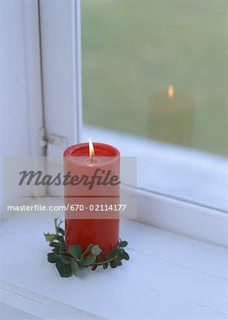 Bougie rouge sur le rebord d'une fenêtre